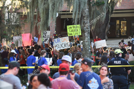 Demonstrators protest from campus before a speech by Donald Trump, Jr. at the University of Florida.