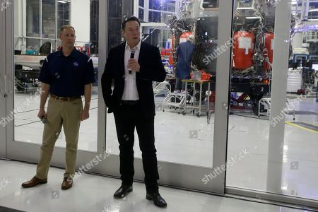 SpaceX chief engineer Elon Musk, right, talks to the media with NASA Administrator Jim Bridenstine, left, in front of the Crew Dragon spacecraft, about the progress to fly astronauts to and from the International Space Station, from American soil, as part of the agency's commercial crew program at SpaceX headquarters, in Hawthorne, Calif