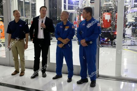 SpaceX chief engineer Elon Musk, second from left, talks to the media with NASA Administrator Jim Bridenstine, left, and NASA astronauts crew Doug Hurley and Bob Behnken, right, in front of the Crew Dragon spacecraft, about the progress to fly astronauts to and from the International Space Station, from American soil, as part of the agency's commercial crew program at SpaceX headquarters, in Hawthorne, Calif