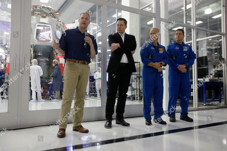 NASA Administrator Jim Bridenstine, left, talks to the media with SpaceX chief engineer Elon Musk, second from left, and NASA astronauts crew Doug Hurley and Bob Behnken, right, in front of the Crew Dragon spacecraft, about the progress to fly astronauts to and from the International Space Station, from American soil, as part of the agency's commercial crew program at SpaceX headquarters, in Hawthorne, Calif