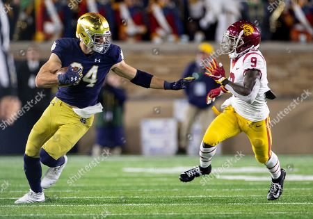 Notre Dame tight end Cole Kmet (84) runs with the ball after the catch as USC defensive back Greg Johnson (9) pursues during NCAA football game action between the USC Trojans and the Notre Dame Fighting Irish at Notre Dame Stadium in South Bend, Indiana. Notre Dame defeated USC 30-27