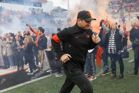 Stock Photo of Oregon State head coach Jonathan Smith runs onto the field prior to the first half of an NCAA college football game against Utah in Corvallis, Ore., . Utah won 52-7