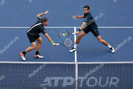 Mate Pavic, Bruno Soares. Mate Pavic of Croatia, right, hits a return shot next to his partner Bruno Soares of Brazil during their men's doubles final against Lukasz Kubot of Poland and Marcelo Melo of Brazil at the Shanghai Masters tennis tournament at Qizhong Forest Sports City Tennis Center in Shanghai, China