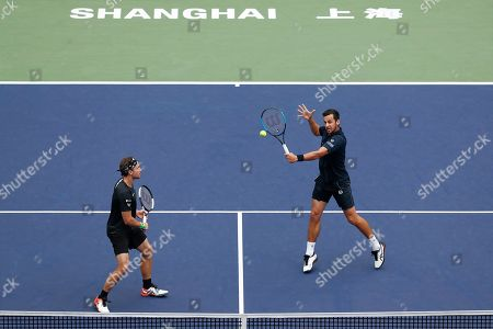 Mate Pavic, Bruno Soarer. Mate Pavic of Croatia, right, hits a return shot next to his partner Bruno Soares of Brazil during their men's doubles final against Lukasz Kubot of Poland and Marcelo Melo of Brazil at the Shanghai Masters tennis tournament at Qizhong Forest Sports City Tennis Center in Shanghai, China