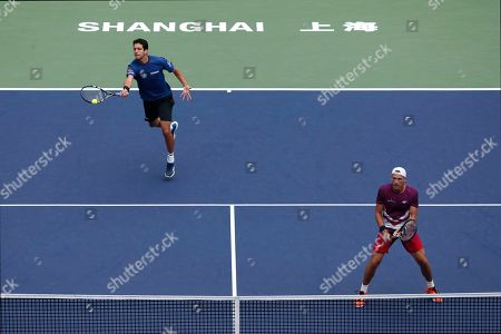 Marcelo Melo, Lukasz Kubot. Marcelo Melo of Brazil, left, hits a return shot next to his partner Lukasz Kubot of Poland during their men's doubles final against Mate Pavic of Croatia and Bruno Soares of Brazil at the Shanghai Masters tennis tournament at Qizhong Forest Sports City Tennis Center in Shanghai, China