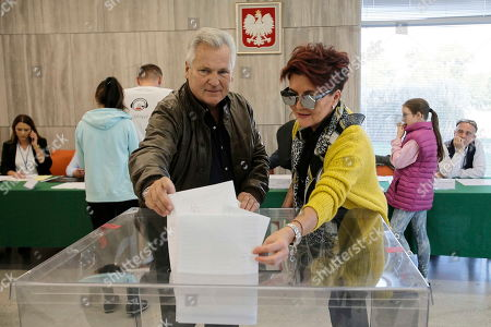 Stock Photo of Former Polish President Aleksander Kwasniewski with his wife Jolanta at a polling station during the parliamentary elections in Warsaw, Poland, 13 October 2019. An average of eleven candidates are running for each Sejm (lower house) seat in the national elections. In total, 5,114 people are running for 460 seats. Two hundred and seventy-eight people are running for the Senate (upper house), three candidatures for each seat. Five electoral committees were registered in all 41 constituencies, namely, the ruling Law and Justice (PiS) party, Poland's main opposition bloc the Civic Coalition (KO), the Polish People's Party (PSL) with Kukiz'15 party, the Confederation Freedom and Independence and the Left (Lewica) bloc comprising liberal and left-wing parties the Democratic Left Alliance (SLD), Spring and Together.