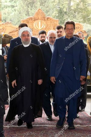 In this photo released by the official website of the office of the Iranian Presidency, Pakistani Prime Minister Imran Khan, right, is welcomed by Iranian President Hassan Rouhani at the Saadabad Palace in Tehran, Iran