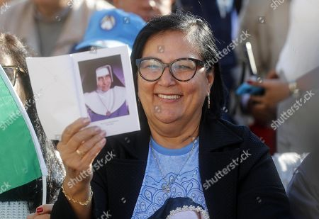 A faithful with a picture of Dulce Lopes Pontes during the canonization Mass of five new Saints in St. Peters Square at the Vatican, 13 October 2019. Five new Saints are canonized at the Vatican on 13 October 2019, namely Brazilian Sister Dulce Lopes Pontes, Swiss Franciscan tertiary Marguerite Bays, Sister Giuseppina Vannini, India's Mother Mariam Thresia Mankidiyan, and British Cardinal John W. Henry Newman.
