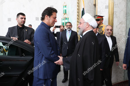 A handout photo made available by the presidential office shows Iranian President Hassan Rouhani (R) greets Pakistani Prime Minister Imran Khan (L) at presidential palace in Tehran, Iran, 13 October 2019. Media reported that Imran Khan is in Tehran to meet with Iranian officials.