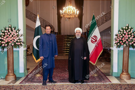 A handout photo made available by the presidential office shows Iranian President Hassan Rouhani (R) receiving Pakistani Prime Minister Imran Khan (L) at presidential palace in Tehran, Iran, 13 October 2019. Media reported that Imran Khan is in Tehran to meet with Iranian officials.