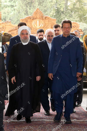 A handout photo made available by the presidential office shows Iranian President Hassan Rouhani (L) receiving Pakistani Prime Minister Imran Khan (R) at presidential palace in Tehran, Iran, 13 October 2019. Media reported that Imran Khan is in Tehran to meet with Iranian officials.