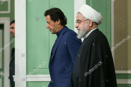 A handout photo made available by the presidential office shows Iranian President Hassan Rouhani (R) and Pakistani Prime Minister Imran Khan (L) arriving for a joint press conference at presidential palace in Tehran, Iran, 13 October 2019. Media reported that Imran Khan is in Tehran to meet with Iranian officials.