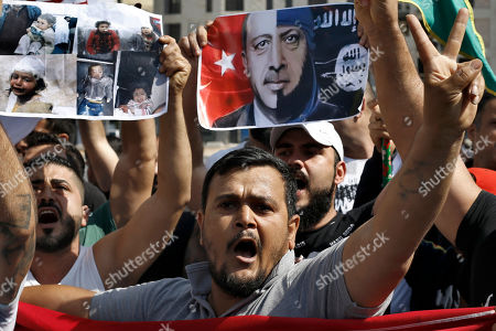 Hundreds of protesters from the Kurdish community in Lebanon, hold a banner depicting Turkish President Recep Tayyip Erdogan, right, as they chant slogans, during a demonstration against Turkey's military operation in northeastern Syria, at Martyrs' Square in downtown Beirut, Lebanon