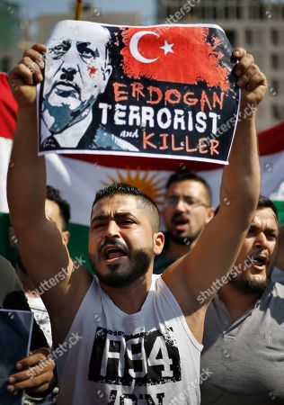 A Kurdish protester holds a banner depicting Turkish President Recep Tayyip Erdogan as he chants slogans during a demonstration against Turkey's military operation in northeastern Syria, at Martyrs' Square in downtown Beirut, Lebanon