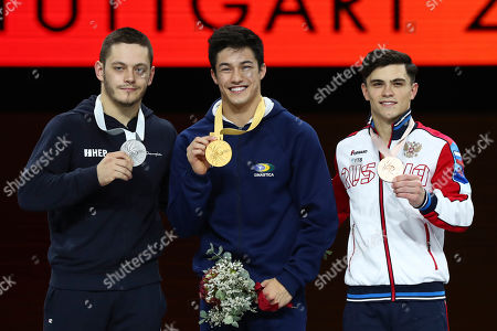 Arthur Mariano of Brazil, center and gold medal, Tin Srbic of Croatia, left, and silver medal, and Artur Dalaloyan of Russia, right and bronze medal, listen to the national anthem during the award ceremony for the horizontal bar exercise in the men's apparatus finals at the Gymnastics World Championships in Stuttgart, Germany