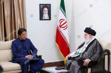 In this picture released by the official website of the office of the Iranian supreme leader, Supreme Leader Ayatollah Ali Khamenei, right, meets Pakistani Prime Minister Imran Khan in Tehran, Iran, . A portrait of the late Iranian revolutionary founder Ayatollah Khomeini hangs on the wall