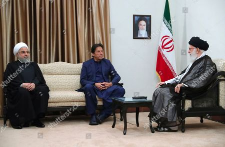 In this picture released by an official website of the office of the Iranian supreme leader, Supreme Leader Ayatollah Ali Khamenei, right, meets Pakistani Prime Minister Imran Khan, center, with Iranian President Hassan Rouhani, in Tehran, Iran, . A portrait of the late Iranian revolutionary founder Ayatollah Khomeini hangs on the wall