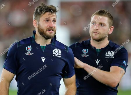 Scotland's Tommy Seymour, left, is consoled by teammate Finn Russell following their 28-21 loss to Japan in their Rugby World Cup Pool A game at International Stadium in Yokohama, Japan