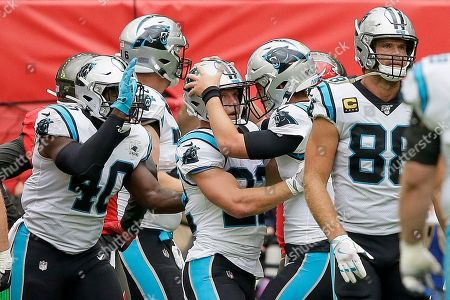 Carolina Panthers running back Christian McCaffrey (22) is congratulated by quarterback Kyle Allen after scoring a touchdown against the Tampa Bay Buccaneers during the first quarter of an NFL football game, at Tottenham Hotspur Stadium in London