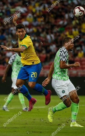 Roberto Firmino (L) of Brazil in action against William Troost-Ekong (R) of Nigeria during an international friendly match between Brazil and Nigeria at the National Stadium in Singapore, 13 October 2019.