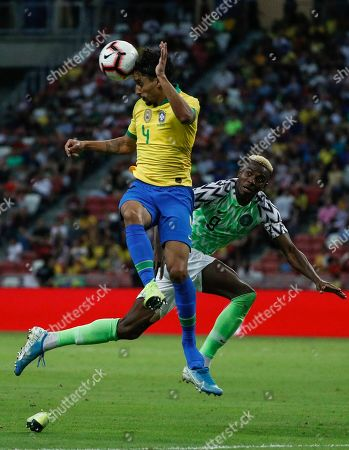 Marquinhos (L) of Brazil in action against Oghenekaro Etebo (R) of Nigeria during an international friendly match between Brazil and Nigeria at the National Stadium in Singapore, 13 October 2019.