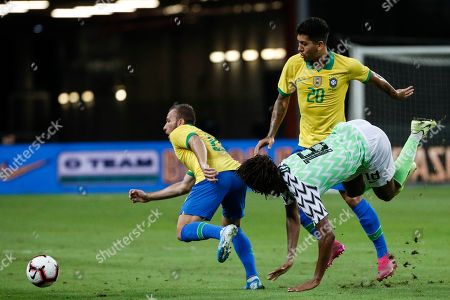 Stock Photo of Roberto Firmino of Brazil (C) and Alex Iwobi of Nigeria (R) in action during an international friendly match between Brazil and Nigeria at the National Stadium in Singapore, 13 October 2019.