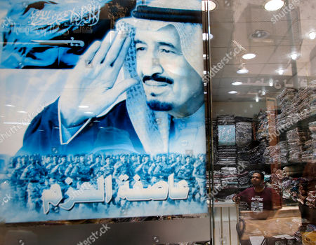 """A vendor waits for clients inside his shop behind a poster showing Saudi King Salman with Arabic that reads, """"Decisive Storm"""" in the historical Old City, of Jiddah, Saudi Arabia"""