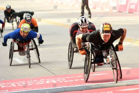 David Weir right, of Britain, finishes second during the men's wheelchair part of the Chicago Marathon, in Chicago