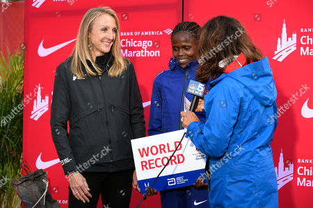 Brigid Kosgei of Kenya, center, talks with the media after breaking the world record with a time of 2:14:04 while former record holder Paula Radcliffe, left, looks on after the women's part of the Chicago Marathon, in Chicago