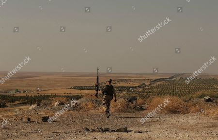 Stock Picture of From the Turkish side of the border between Turkey and Syria, in Ceylanpinar, Sanliurfa province, southeastern Turkey, a Turkish soldier walks toward Ras al-Ayn, Syria, . Turkey's President Recep Tayyip Erdogan has rejected offers for mediation with Syrian Kurdish fighters as the Turkish military continues its offensive against them in northern Syria