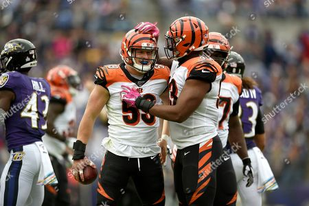 Cincinnati Bengals outside linebacker Nick Vigil (59) is congratulated by defensive tackle Andrew Brown (93) after recovering a fumble by Baltimore Ravens tight end Mark Andrews during the first half of a NFL football game, in Baltimore