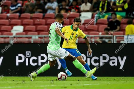 Stock Photo of Brazil's Philippe Coutinho, right, and Nigeria's William Troost-Ekong in action during the Brazil Global Tour 2019 international friendly match between Brazil and Nigeria in Singapore