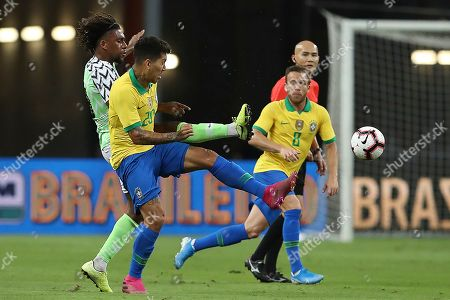 Brazil's Roberto Firmino and Nigeria's Alex Iwobi, rear left, in action during the Brazil Global Tour 2019 international friendly match between Brazil and Nigeria in Singapore