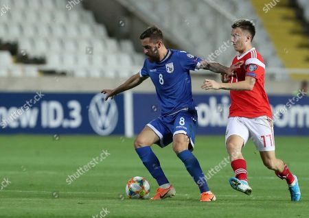 Cyprus' Chambos Kyriakou, left, duels for the ball with Russia's Aleksandr Golovin during the Euro 2020 group I qualifying soccer match between Cyprus and Russia at Georges St-Pierre stadium in Nicosia, Cyprus