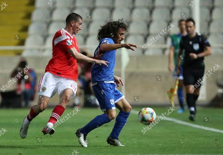 Cyprus' Margaca, center, duels for the ball with Russia's Aleksei Ionov during the Euro 2020 group I qualifying soccer match between Cyprus and Russia at Georges St-Pierre stadium in Nicosia, Cyprus