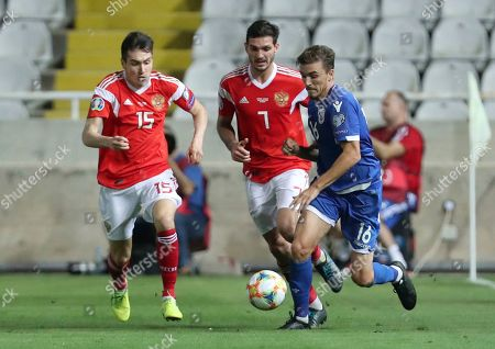 Cyprus' Matija Spoljaric, right, Russia's Magomed Ozdoev, center, and Russia's Vyacheslav Karavaev run for the ball during the Euro 2020 group I qualifying soccer match between Cyprus and Russia at Georges St-Pierre stadium in Nicosia, Cyprus