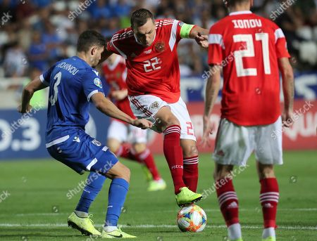 Russia's Artem Dzyuba, center, duels for the ball with Cyprus' Nicholas Ioannou, left, during the Euro 2020 group I qualifying soccer match between Cyprus and Russia at Georges St-Pierre stadium in Nicosia, Cyprus