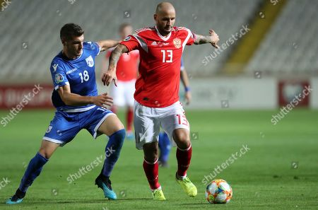 Russia's Fedor Kudryashov, right, duels for the ball with Cyprus' Kostakis Artymatas during the Euro 2020 group I qualifying soccer match between Cyprus and Russia at Georges St-Pierre stadium in Nicosia, Cyprus