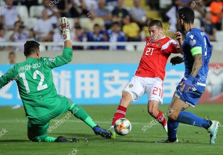 Cyprus' goalkeeper Urko Pardo, left, makes a save in front of Russia's Aleksei Ionov, center, during the Euro 2020 group I qualifying soccer match between Cyprus and Russia at Georges St-Pierre stadium in Nicosia, Cyprus