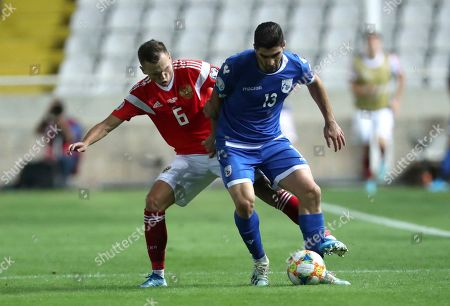 Russia's Denis Cheryshev, left, duels for the ball with Cyprus' Ioannis Kousoulos during the Euro 2020 group I qualifying soccer match between Cyprus and Russia at Georges St-Pierre stadium in Nicosia, Cyprus