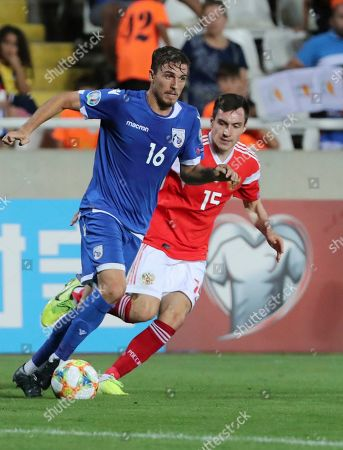Cyprus' Matija Spoljaric, left, and Russia's Vyacheslav Karavaev run for the ball during the Euro 2020 group I qualifying soccer match between Cyprus and Russia at Georges St-Pierre stadium in Nicosia, Cyprus