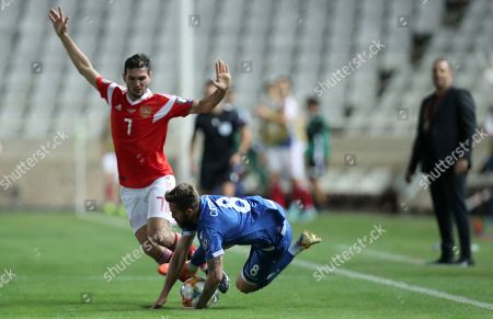 Cyprus' Chambos Kyriakou, front, duels for the ball with Russia's Magomed Ozdoev during the Euro 2020 group I qualifying soccer match between Cyprus and Russia at Georges St-Pierre stadium in Nicosia, Cyprus