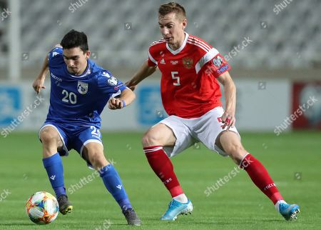 Cyprus' Ioannis Costi, left, duels for the ball with Russia's Andrei Semenov during the Euro 2020 group I qualifying soccer match between Cyprus and Russia at Georges St-Pierre stadium in Nicosia, Cyprus