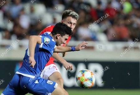 Cyprus' Ioannis Costi, left, tries to block a shot from Russia's Aleksandr Golovin during the Euro 2020 group I qualifying soccer match between Cyprus and Russia at Georges St-Pierre stadium in Nicosia, Cyprus