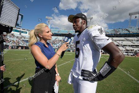 CBS television sideline reporter Melanie Collins interviews New Orleans Saints quarterback Teddy Bridgewater (5) after an NFL football game against the Jacksonville Jaguars, in Jacksonville, Fla