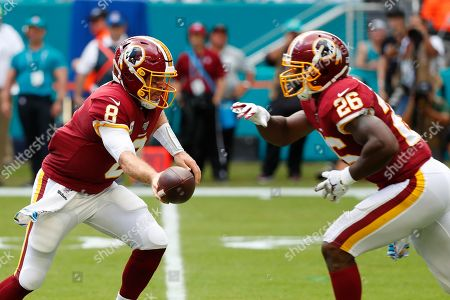 Case Keenum, Adrian Peterson. Washington Redskins quarterback Case Keenum (8) hands the ball to running back Adrian Peterson (26), during the first half at an NFL football game against the Miami Dolphins, in Miami Gardens, Fla