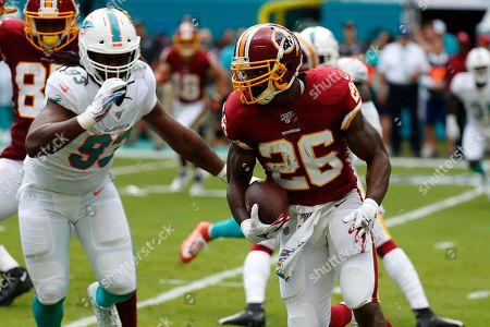 Washington Redskins running back Adrian Peterson (26) runs the ball, during the first half at an NFL football game against the Miami Dolphins, in Miami Gardens, Fla