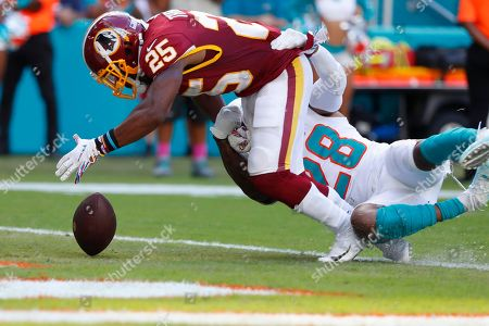 Bobby McCain, Adrian Peterson. Miami Dolphins strong safety Bobby McCain (28) forces Washington Redskins running back Adrian Peterson (26) to drop a pass in the end zone, during the second half at an NFL football game, in Miami Gardens, Fla