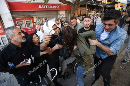 Security officials detain a pro-Kurdish party member who is protesting against Turkey's military operation in Syria, in Istanbul, . Turkey's President Recep Tayyip Erdogan has rejected offers for mediation with Syrian Kurdish fighters as the Turkish military continues its offensive against them in northern Syria