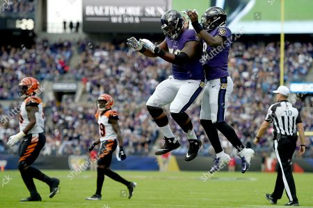 Baltimore Ravens offensive tackle Ronnie Stanley, left, and quarterback Lamar Jackson celebrate Jackson's touchdown run against the Cincinnati Bengals during the first half of a NFL football game, in Baltimore